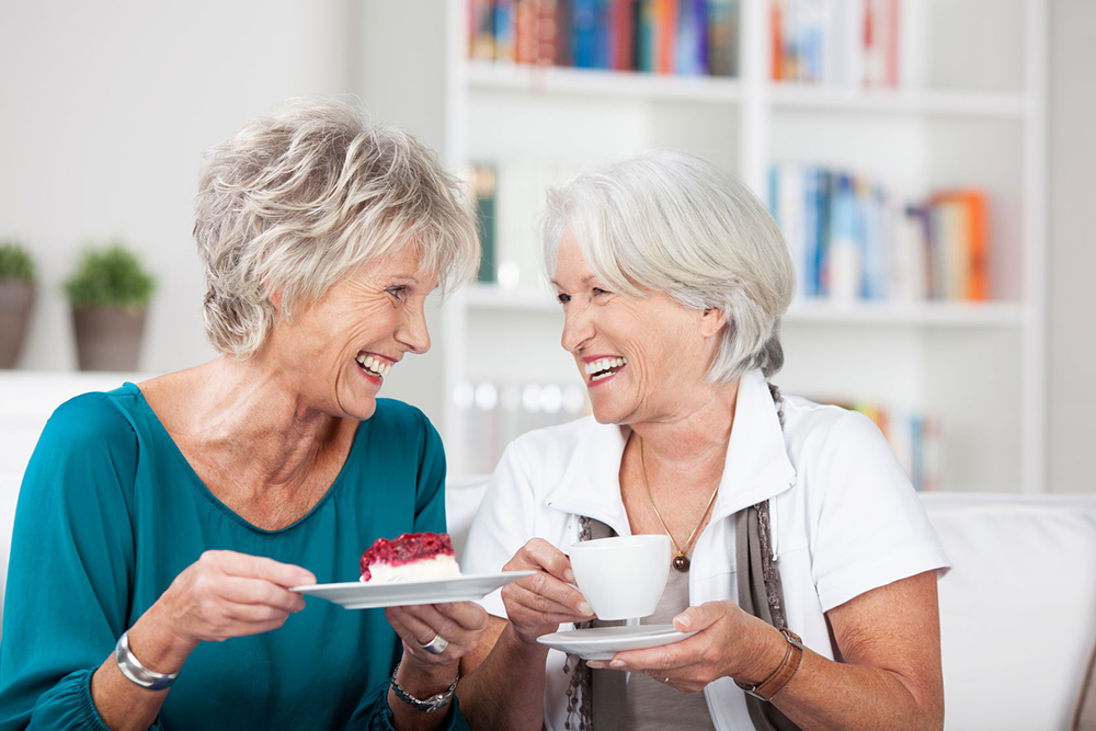 two friends eating cake and drinking coffee